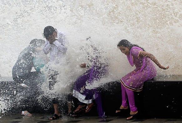 People enjoy high tide waves during monsoon rains on the Arabian Sea coast in Mumbai.