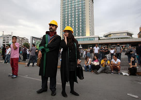A couple of lawyers wearing yellow helmets take part in protest at Taksim Square in Istanbul.