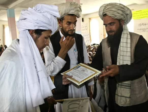 An Afghan man hands a certificate to a student as he graduates from a local Islamic school or madrassa, during a graduation ceremony at the Mazharal Olom mosque in Ghazni province west of Kabul, Afghanistan.