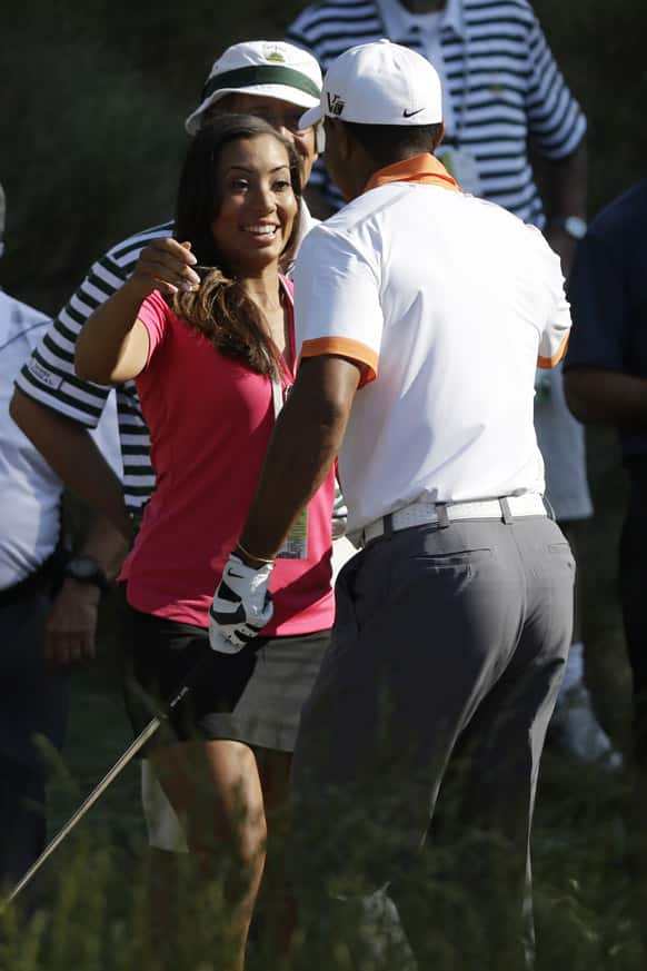 Tiger Woods greets his niece, Cheyenne Woods, near the 18th tee during practice for the US Open golf tournament at Merion Golf Club in Ardmore, Pa.
