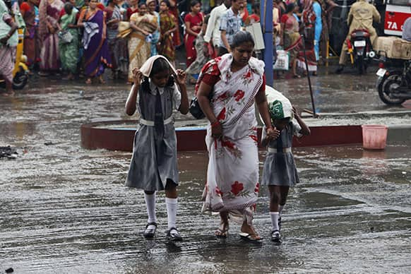 Children protect themselves while crossing a road with their mother during rain in Hyderabad.