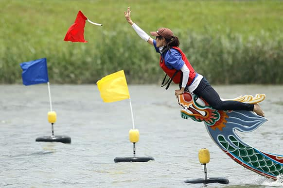 The winning team tosses the flag during the annual Chinese traditional Dragon Boat Festival races in Taipei, Taiwan.