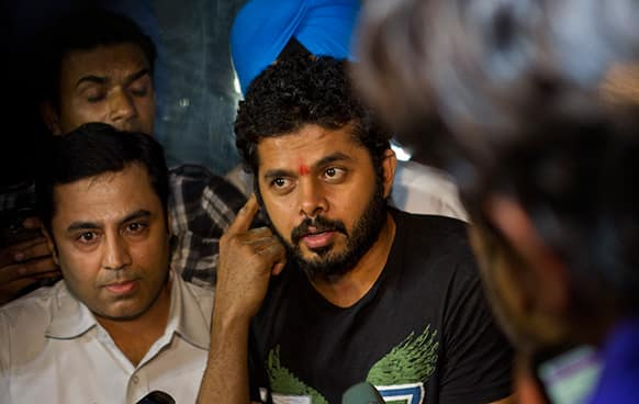 Indian cricket player Shantakumaran Sreesanth, center, who on May 16 was arrested along with two other players on spot fixing charges, talks to the media after he was released from prison in New Delhi.