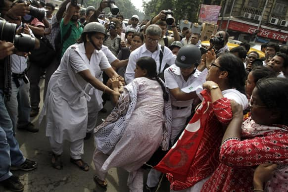 Women activists of Socialist Unity Center of India (SUCI) tussle with police as they block traffic during a protest against a gang-rape and murder of a girl at suburban Barasat, in Kolkata.