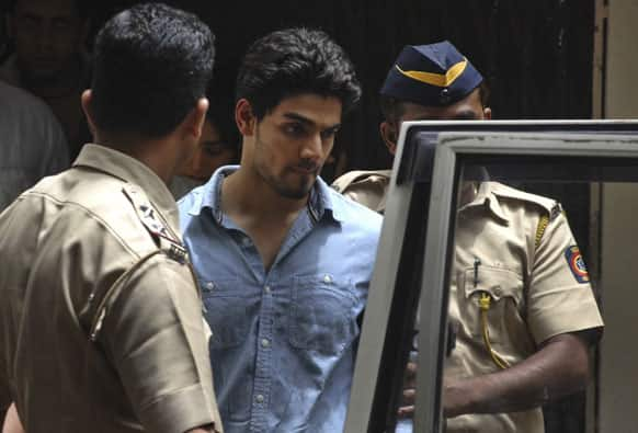 Suraj Pancholi, the son of Bollywood couple Aditya Pancholi and Zarina Wahab is escorted by police as he leaves after appearing before a court in Mumbai.