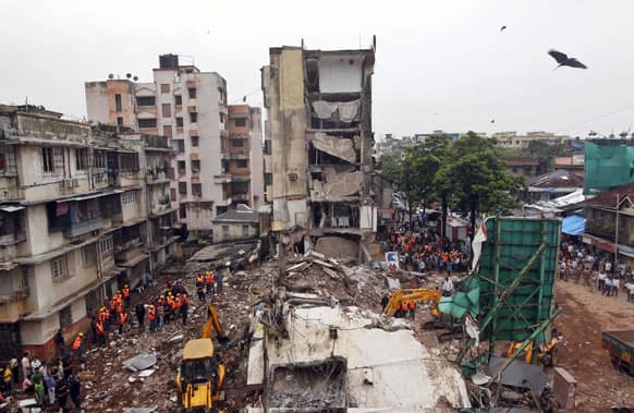 Rescue workers search for trapped people after a residential building collapsed in Mumbai. A portion of a four-story building in India`s financial capital collapsed in heavy monsoon rains, killing some people Tuesday.