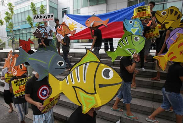Protesters wearing fish-shaped hats walk outside the Chinese Consulate during a rally in suburban Makati, south of Manila, Philippines.