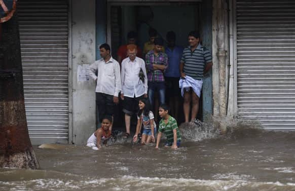 People take shelter by a wayside building as children play in water during monsoon rains in Mumbai.