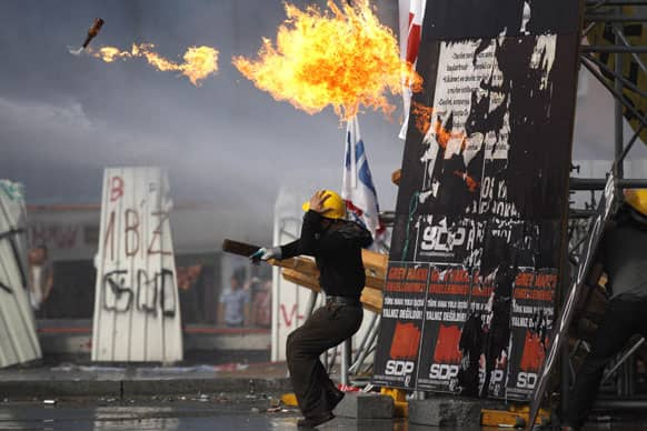 A protester throws a petrol bomb towards riot policemen during clashes in Taksim Square in Istanbul, Turkey.