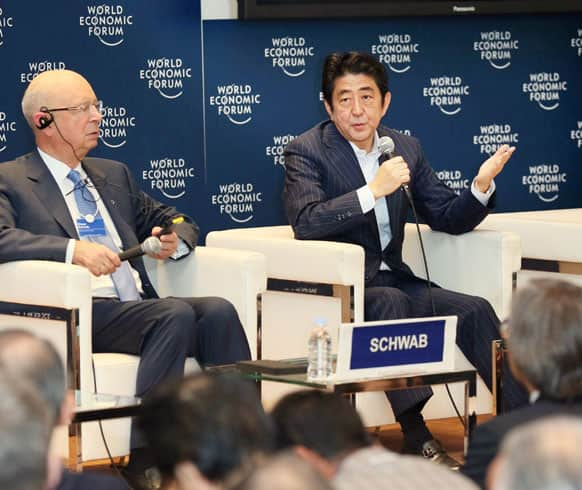 Japanese Prime Minister Shinzo Abe, accompanied by World Economic Forum founder and executive chairman Klaus Schwab, speaks during a World Economic Forum meeting in Tokyo.