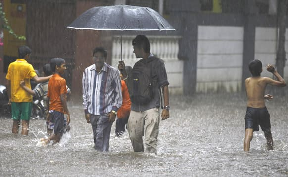 Children play as two men walk through a flooded street during monsoon rains in Mumbai. The Southwest monsoon, arrived in the city, three days ahead of schedule, according to the meteorological department.
