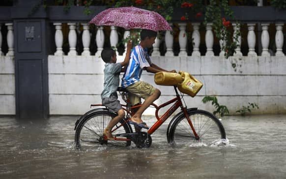 Two boys ride a bicycle through a flooded street during monsoon rains in Mumbai.