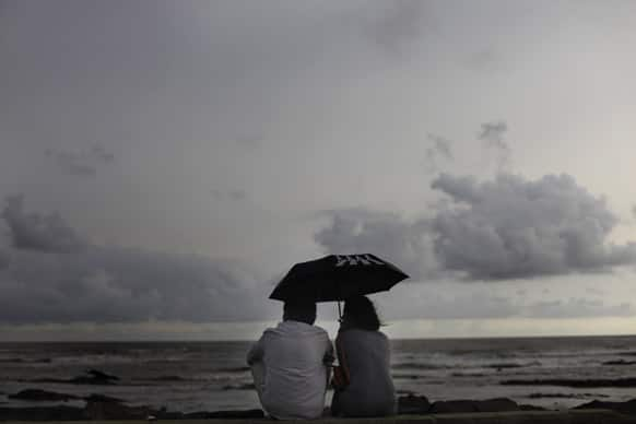 A couple sit along the shores of the Arabian Sea on a cloudy day, in Mumbai.