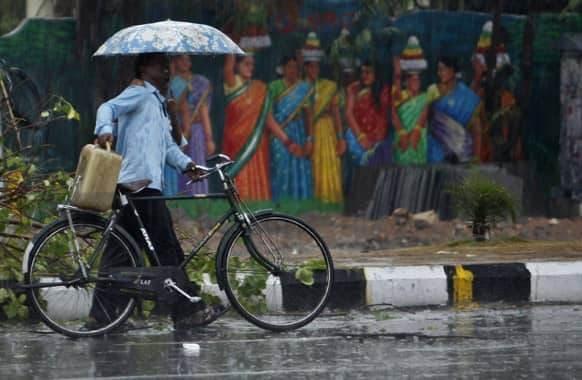 A cyclist and a pedestrian share an umbrella as they walk past a painted wall during sudden rainfall in Hyderabad.