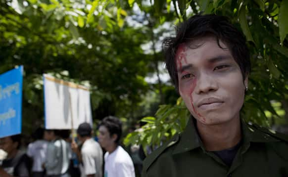 A peace activist with painted face symbolizing a victim of the civil war between the Ethnic Kachin fighters and Myanmar government security forces participates in a peace march marking the second anniversary of the resumption of the fighting between Kachin rebels and government forces, in Yangon.