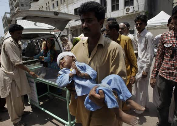 A Pakistani child who was injured in a cross firing incident of two rival groups is brought to a local hospital for treatment in Karachi.