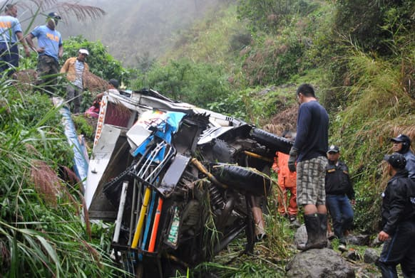 Police officers inspect the wreckage of a van that veered off a mountain road in the remote Buguias town in Benguet province, northern Philippines.