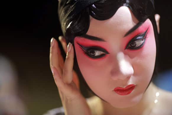 A Beijing Opera actress applies makeup at the back stage before the show begins in Shanghai, China.