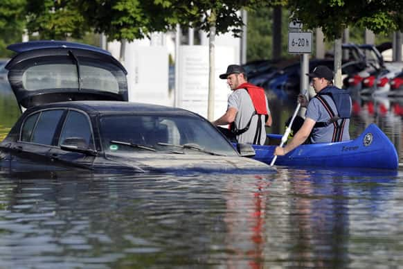 Two men in a boat look at a car standing in the flood of river Danube in Deggendorf, southern Germany.