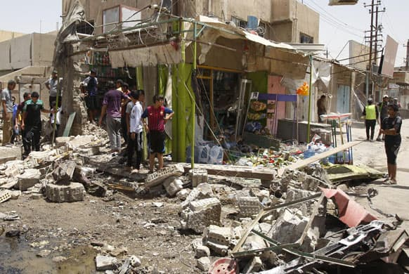 Civilians inspect the scene of a car bomb attack at al-Ameen neighborhood in Baghdad, Iraq.
