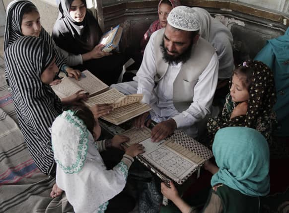 Afghan teacher Matiullah, teaches children how to read Quran, Islam`s holy book, at a local madrassa, or seminary, in Jalalabad, east of Kabul, Afghanistan.