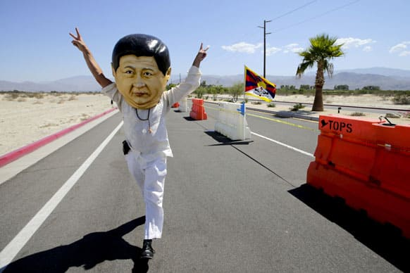 Giovanni Vassallo, of San Francisco, wears a giant mask depicting Chinese President Xi Jinping near the Annenberg Retreat at Sunnylands in Rancho Mirage , Calif.