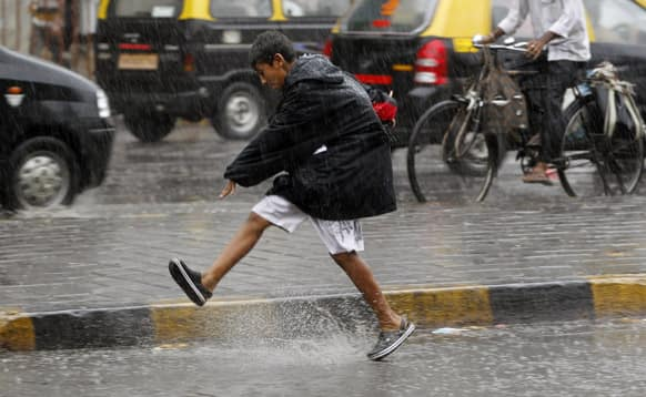 A young boy enjoys a spell of heavy rain shower as he crosses a street in Mumbai.