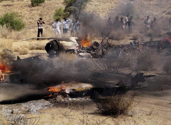 People watch the burning wreckage of a MiG-21 jet of the Indian Air Force near Sodiyar village in Barmer district of the western Indian state of Rajasthan. No casualties were reported as the pilot of the fighter jet ejected safely, according to a local news agency.