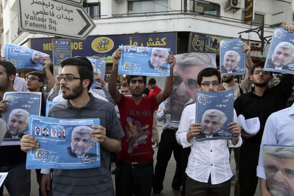 Supporters of the Iranian presidential candidate Saeed Jalili, shown in the posters, who is also Iran`s top nuclear negotiator, attend a street campaign, in Tehran, Iran.