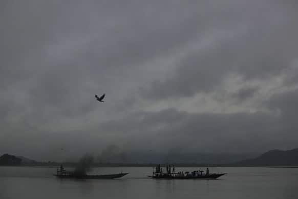 Monsoon clouds hover over boats sailing in the Brahmaputra River in Guwahati.