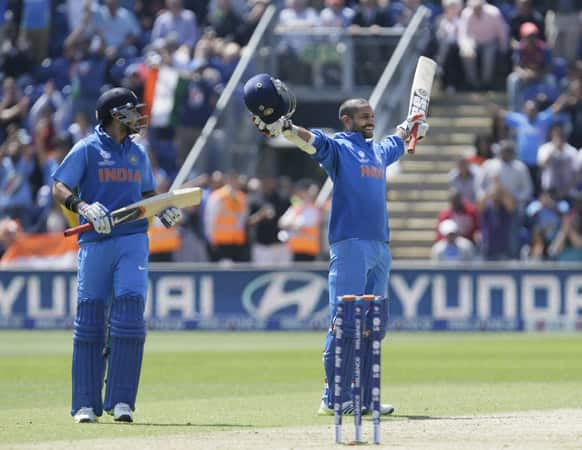 Shikhar Dhawan reacts as he reaches 100 runs not out, watched by teammate Virat Kohli as they play against South Africa during their group stage ICC Champions Trophy cricket match in Cardiff, Wales.