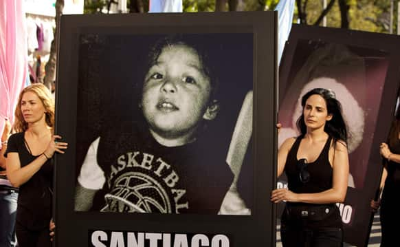 Women carry photographs of children who died in a 2009 daycare fire as they protest on the fourth anniversary of the blaze in Mexico City.