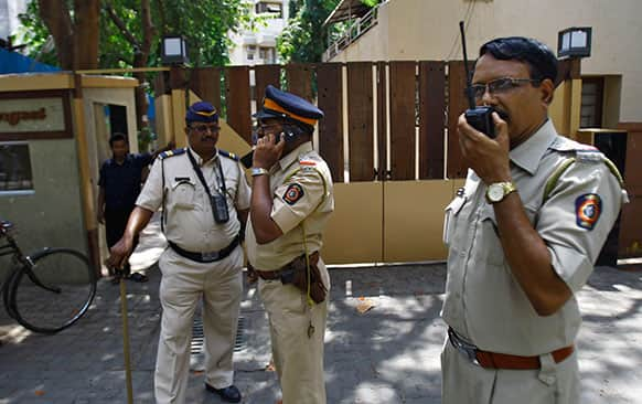 Police men speak on a wireless radio as they stand outside a complex that houses the home of Bollywood actress Jiah Khan in Mumbai.