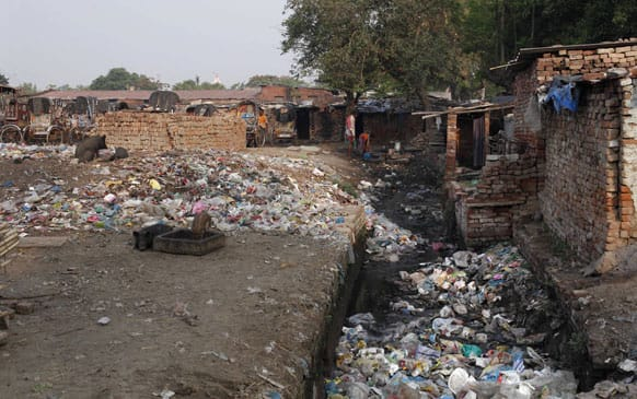 People collect drinking water from a pipe beside a sewage polluted with plastic and other garbage in Allahabad.
