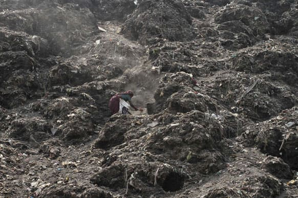 A woman, searches for reusable material amid a mountain of garbage at a dump in Ahmadabad.