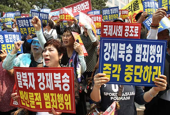 Members of Korea Freedom Federation shout slogans during a rally to demand the safety of North Korean defectors, in Seoul, South Korea.