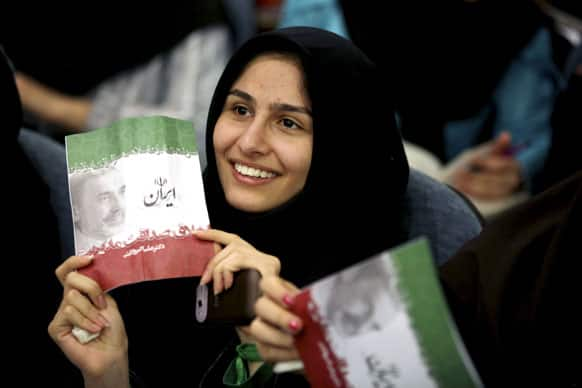 A supporter of Iranian presidential candidate, Ali Akbar Velayati, a conservative former Foreign Minister, holds up an electoral leaflet, during a campaign meeting, at the Beheshti University, in Tehran, Iran.