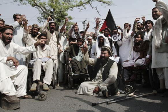 Afghan disabled people chant slogans during a demonstration in front of the governor house of Jalalabad, east of Kabul, Afghanistan.