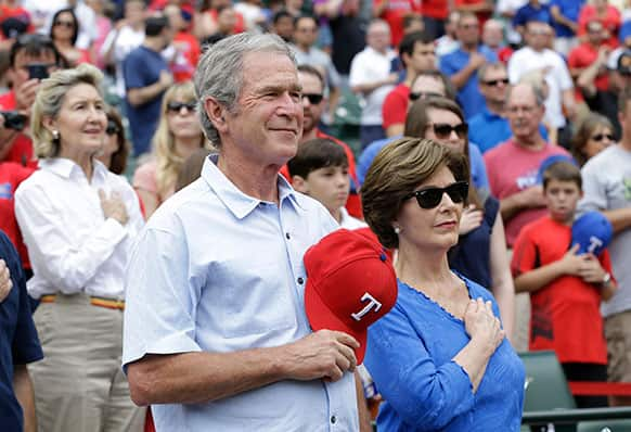 Former President George W. Bush stands during the national anthem with his wife Laura Bush before a baseball game between the Kansas City Royals and Texas Rangers in Arlington.