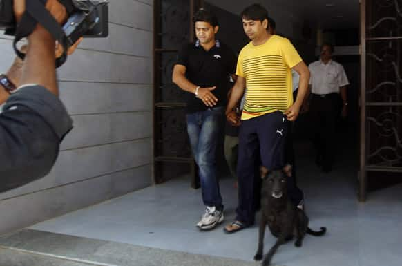 A Mumbai Crime Branch official, left in black, escorts bookie Ashwin Agarwal to the Esplande court for spot fixing in cricket, in Mumbai.