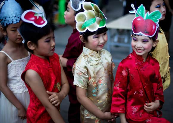 Children wearing costumes wait to participate in a stage show on International Children`s Day organized by the Chinese Foreign Affairs Office at Children`s Palace of Dongcheng district in Beijing.