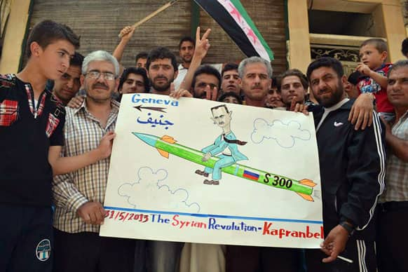 This image provided by Edlib News Network, which has been authenticated based on its contents and other AP reporting, show anti-Syrian regime protesters holding a placard with a sarcastic caricature on it against Syrian President Bashar Assad, during a demonstration, at Kafr Nabil town, in Idlib province.