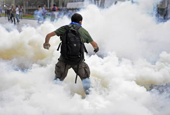 A man runs as riot police use tear gas and pressurized water to quash a peaceful demonstration by hundreds of people staging a sit-in protest to try and prevent the demolition of trees at an Istanbul park.