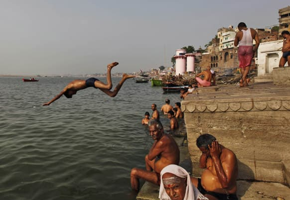 An Indian boy jumps into the River Ganges to beat the heat in Varanasi. With the onset of summer many parts of northern India are facing heat wave conditions.