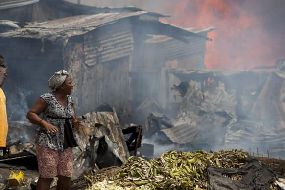 A Haitian merchant reacts as she watches flames engulf her belongings at Port Market in Port-au-Prince, Haiti.