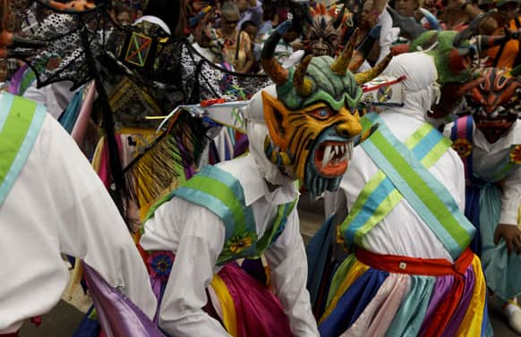 Dancers wearing a traditional devil mask and costumes dance during Corpus Christi celebrations in the streets of La Villa, Panama.