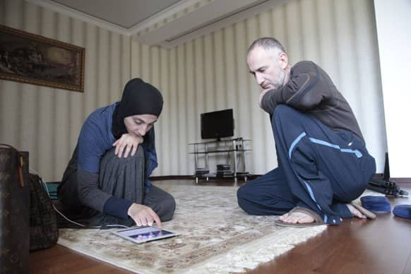 Zubeidat Tsarnaeva, left, and husband Anzor Tsarnaev show videos on an iPad they say show their sons could not have been involved in last month`s Boston Marathon bombings in their new apartment in Makhachkala, regional capital of Dagestan, Russia.