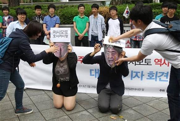South Korean college students crack eggs on masks of Japanese Prime Minister Shinzo Abe and Japan`s Osaka Mayor Toru Hashimoto, left, during a rally against Japan in front of the Japanese embassy in Seoul, South Korea.