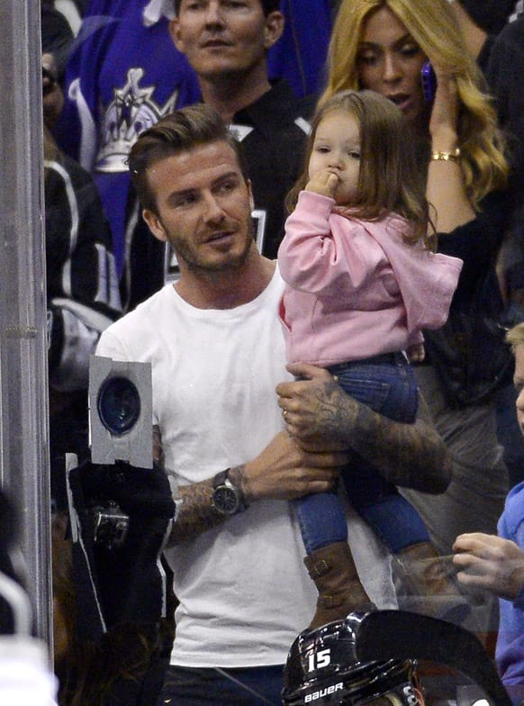 Retired soccer player David Beckham holds his daughter Harper as he watches the Los Angeles Kings play the San Jose Sharks in Game 7 of the Western Conference semifinals in the NHL hockey Stanley Cup playoffs, in Los Angeles.