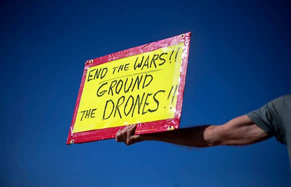 Tom Coffia, of Atlanta, holds a sign out for passing motorists as he takes part in a demonstration protesting against the use of drones outside the International Conference on Unmanned Aircraft Systems at the Grand Hyatt Hotel, in Atlanta.